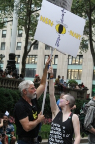 A protester blocks a homophobic counter-protester's sign with another sign.