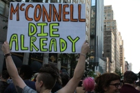 "A protester at The Dyke March holds a sign that says ""McCONNELL DIE ALREADY."""